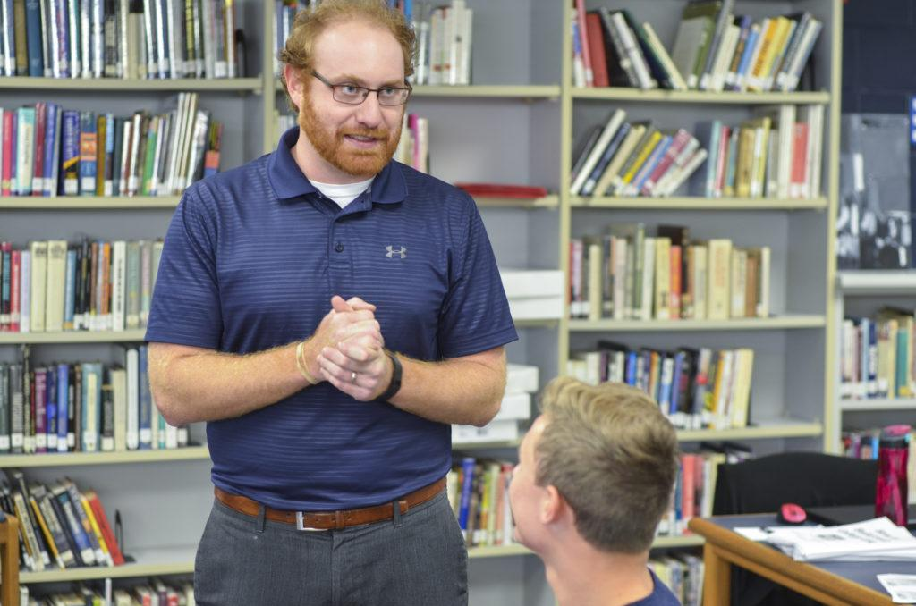 Cody Masters gives advice to a student in the library.