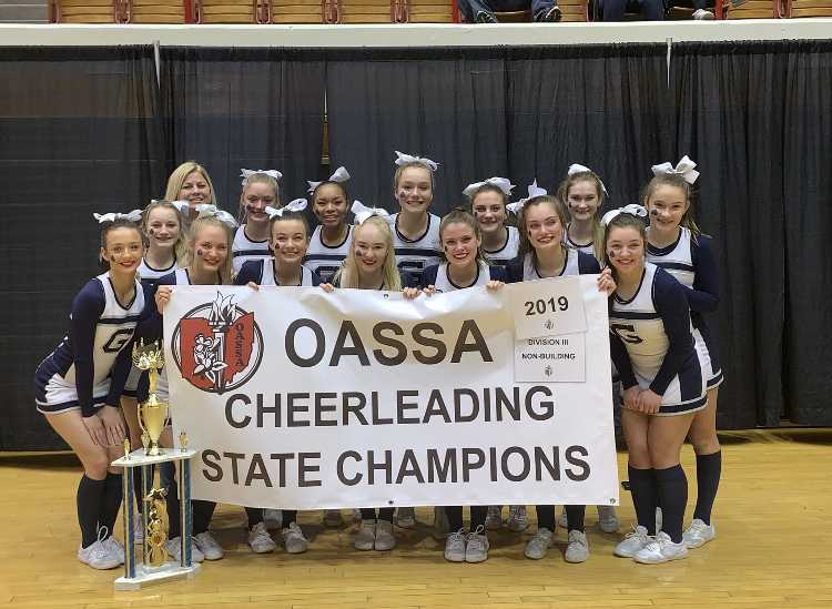 The Blue Aces competition cheer team holds up championship banner after winning the OASSA state title (Photo Courtesy of Granville Cheer Twitter).