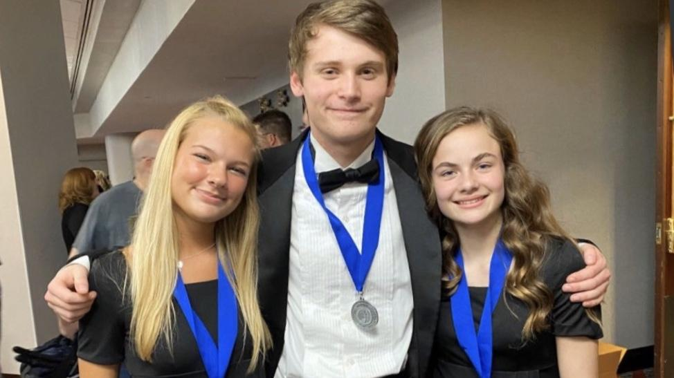 Choir+students+Lanie+Schott%2C+Matthew+Steele+and+Lillian+Reese+smile+after+performing+at+the+OMEA+All-State+conference.+They+received+medals+for+their+handwork+and+dedication.+Photo+courtesy+of+Kristen+Snyder.