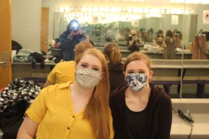 Sophomore Lucy Waggoner (Nina) poses with her sister Roxy, a makeup and costume crew member, pose before all-day tech. Due to Covid-19 regulations, all cast and crew members had to wear masks. BluePrints Photo by Kennedy Ogden