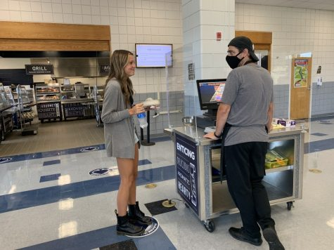 """Senior Kylee Lescas talks to cafeteria worker Adam after buying her lunch. Due to the new grant, more students are buying school lunch which makes the lines a lot longer. """"We are going through roughly 400-500 more full meals a day with this grant,"""" Head Chef Jon Harbaugh said."""
