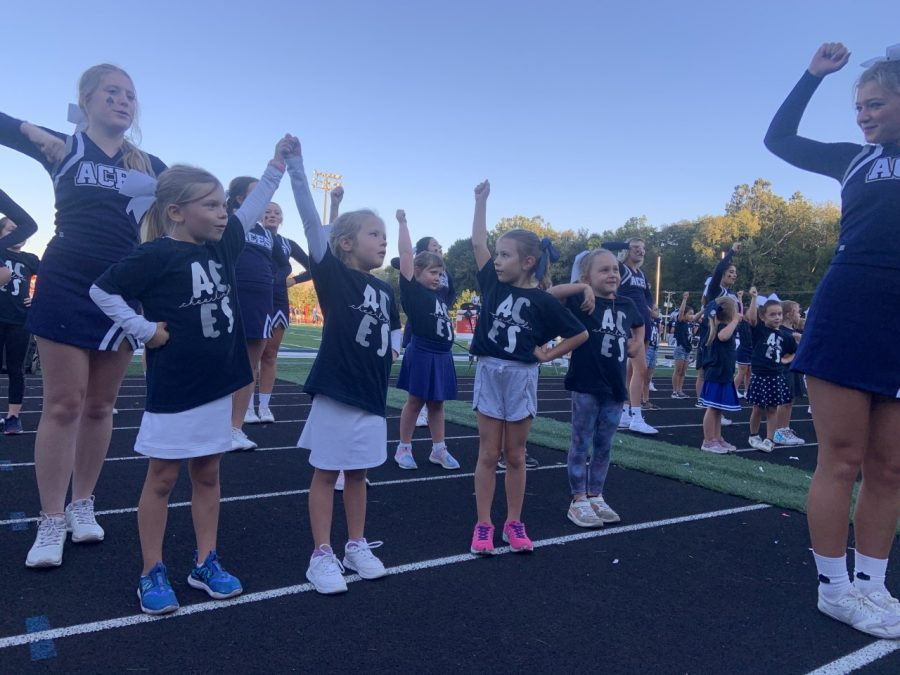 Ella Kunar leads the first grade cheerleaders on the track as they cheer on the football team.
